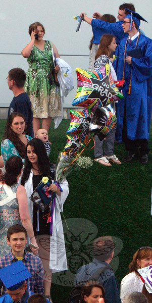 One graduate stands outside the O'Neill Center, clutching her diploma and with an armload of flowers and balloons. (Hicks photo)