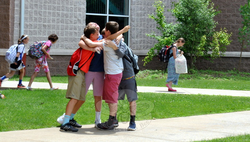 Reed Intermediate School students hugged after leaving the school and board the bus on the last day of the 2014-15 school year. (Hallabeck photo)