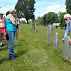 Town Historian Dan Cruson, right, led a group through the Village Cemetery on Sunday, June 14. He stopped at a number of gravestones, including the gravestone for Reuben Booth, pictured. (Hallabeck photo)