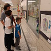 Karen Smiley, left, was escorted by her daughter Lauren and son Andrew to look at art on display for Hawley Elementary School's Art Show, held on Thursday, June 11. (Hallabeck photo)
