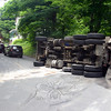 This large construction dump truck flipped over on Botsford Hill Road, near the Housatonic Railroad overpass, early on the afternoon of Saturday, June 20, closing down a section of that road to through-traffic for more than six hours as cleanup work was underway. Police issued violations to the truck's driver and its owner. (Hicks photo)