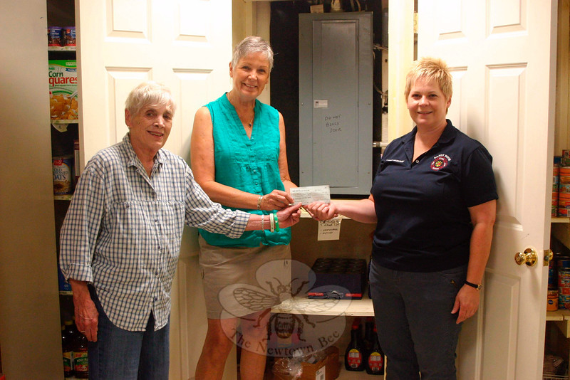 "Sandy Hook Volunteer Fire & Rescue Ladies Auxiliary Treasurer Sharon Doherty, right, visited FAITH Food Pantry this week to deliver a donation on behalf of the auxiliary. The money came from part of the proceeds of the group's recent flower sales, as well as their dessert table during the Sandy Hook LobsterFest earlier this month. ""We thank the community for supporting us, and we wanted to pay back to the community this way,"" Mrs Doherty said. Accepting the check on June 23, was FAITH President Lee Paulsen, left, and Treasurer Barbara Krell. The women are standing in front of the cabi-net usually used to store canned pasta products. It is one of the items the pantry is currently low on. Donations — financial or of nonperishables — are welcomed any time the pantry is open, Tuesdays from 10 am until noon and Thursdays from 6 to 7:30. The nonecumenical pantry is set up in the basement of St John's Episcopal Church, 5 Washington Avenue in Sandy Hook. (Hicks photo)"