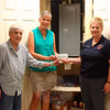 """Sandy Hook Volunteer Fire & Rescue Ladies Auxiliary Treasurer Sharon Doherty, right, visited FAITH Food Pantry this week to deliver a donation on behalf of the auxiliary. The money came from part of the proceeds of the group's recent flower sales, as well as their dessert table during the Sandy Hook LobsterFest earlier this month. """"We thank the community for supporting us, and we wanted to pay back to the community this way,"""" Mrs Doherty said. Accepting the check on June 23, was FAITH President Lee Paulsen, left, and Treasurer Barbara Krell. The women are standing in front of the cabi-net usually used to store canned pasta products. It is one of the items the pantry is currently low on. Donations — financial or of nonperishables — are welcomed any time the pantry is open, Tuesdays from 10 am until noon and Thursdays from 6 to 7:30. The nonecumenical pantry is set up in the basement of St John's Episcopal Church, 5 Washington Avenue in Sandy Hook. (Hicks photo)"""