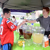Aidan Finnegan accepts a sample cup of lemonade from Riley Rising of Sandy Hook, who had tended the Organic Lemonade and Iced Tea stand Tuesday, June 23, the 2015 Farmers Market on the Fairfield Hills opening day..  (Bobowick photo)