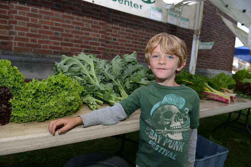 Jesse Shortt, 5, of Shortt's Farm and Garden Center in Sandy Hook off of Riverside Road, helps with produce sales Tuesday, during opening day of the Newtown Farmers Market at Fairfield Hills.  (Bobowick photo)