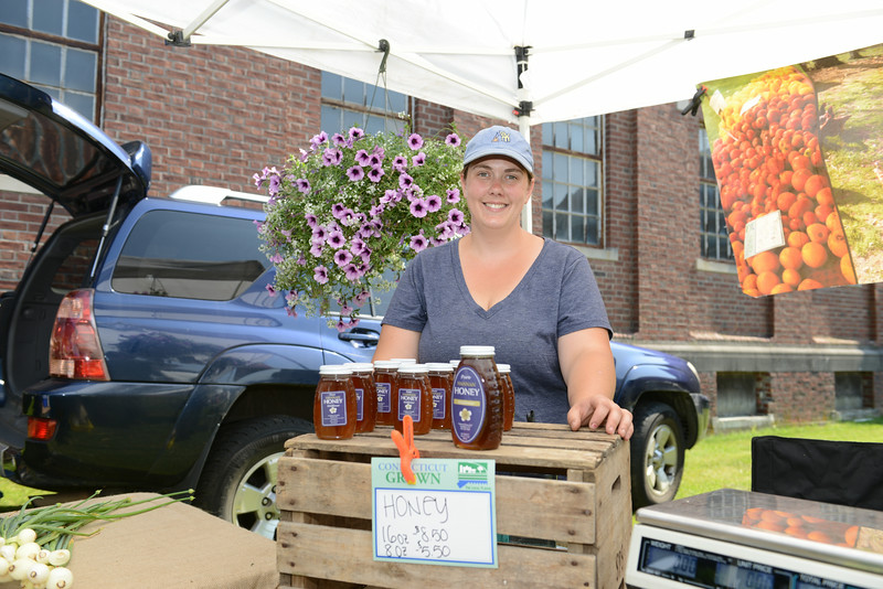 Fresh produce, honey, and hanging baskets were for sale at the Daffodil Growers at Woodside Farm, Southbury, during opening day of the Newtown Farmers Market at Fairfield Hills. Working her family's booth and helping customers was Sara Blersch.  (Bobowick photo)
