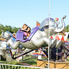 Two young carnivalgoers hold on as their giant flying elephant spins them around.  (Bobowick photo)