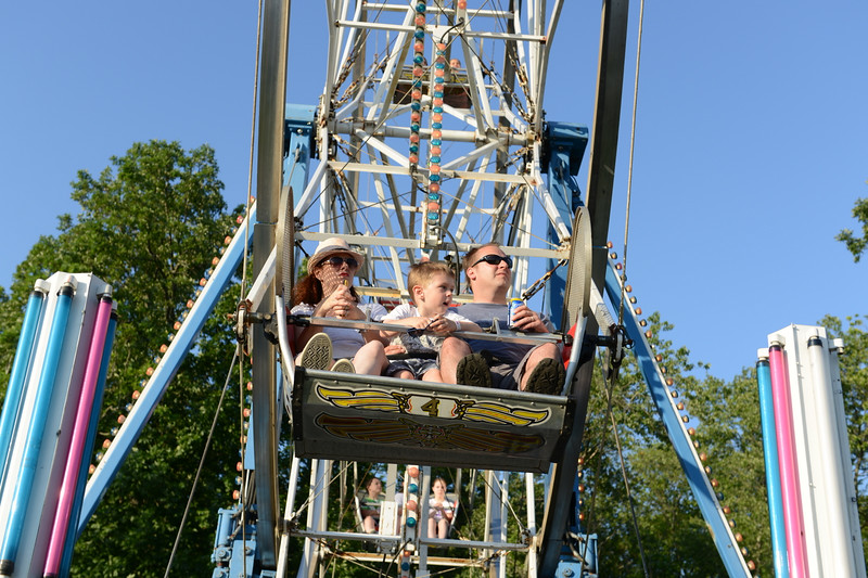 A young boy squeezed between adults looks out over the St Rose field on Tuesday, the opening night of the St Rose Parish Carnival. The annual event runs each night through June 28.  (Bobowick photo)