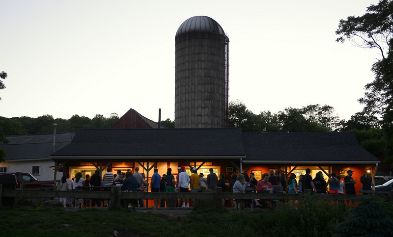 With just a hint of fading daylight in the sky Saturday, June 14, a crowd silhouetted by ice cream shop lights lined the gravel lot at Ferris Acres Creamery on Route 302, waiting to order a cone or sundae. The working farm's silo towers over the single-story structure below where families gather throughout the summer. On Monday, June 23, the ice cream stand celebrated its tenth anniversary.  (Bobowick photo)