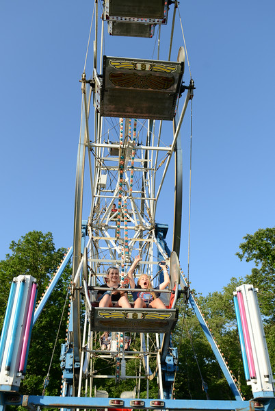 One smiling and the other with her hands up as she shouts, two girls enjoy a spin on the Ferris wheel.  (Bobowick photo)