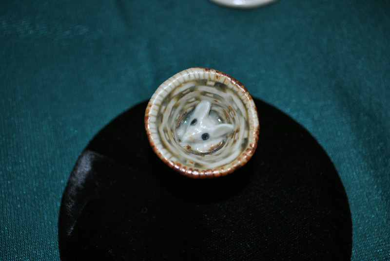 A miniscule mouse peers out of a thimble-sized porcelain basket, one of the porcelain creations by the late Jean Mann currently on view at C.H. booth Library.  (Crevier photo)