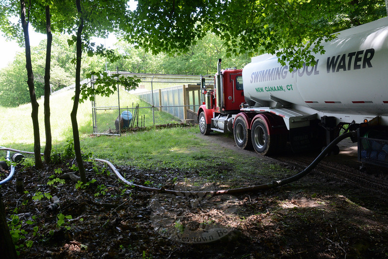 A tanker truck carrying potable water is shown emptying its load into the bunker-style water storage tanks for the Fairfield Hills water supply system midday on Wednesday, June 3. Due to an equipment failure caused by a lightning strike, the pumps that resupply the storage tanks failed, requiring that water be trucked in to replenish the tanks until suitable water system repairs could be made. (Gorosko photo)