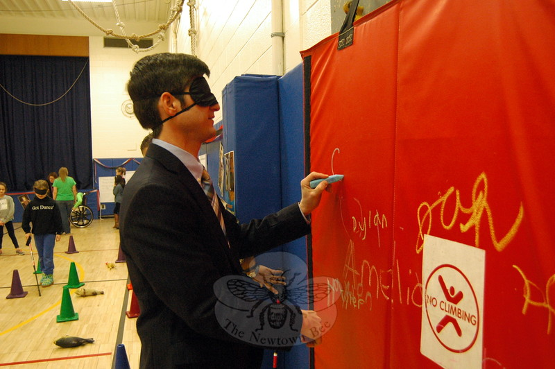 Middle Gate Elementary School Principal Chris Geissler tried his hand at writing his name while blindfolded, which was one of the many activities offered during his school's Differences Day. (Hallabeck photo)