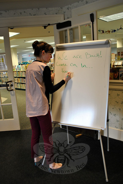 "Candace Woods, library clerk, writes the words on the white board patrons of the C.H. Booth Library Children's Department have been longing to see, since flooding shut it down, February 17: ""We Are Back!"" The department reopened to the public Friday, March 13. (Crevier photo)"