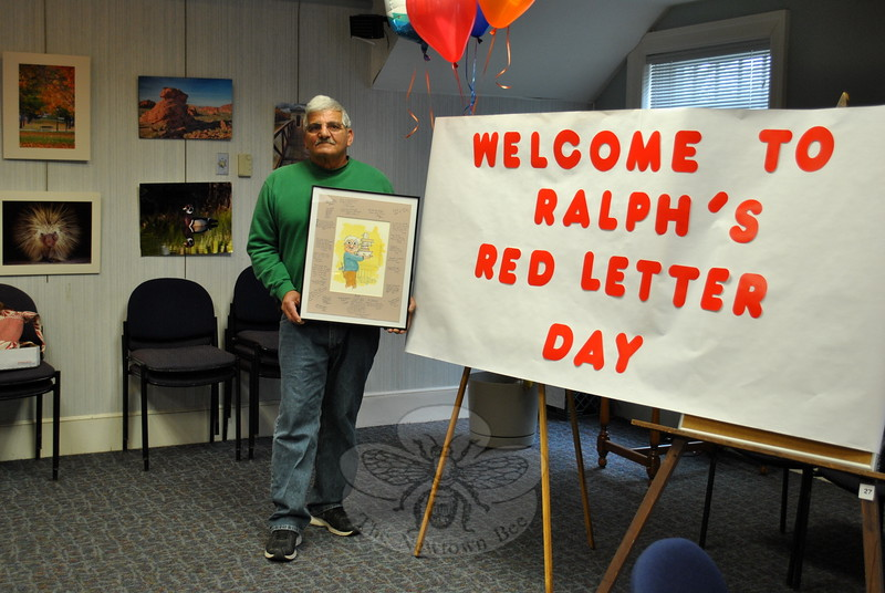 Ralph Scogno, longtime Booth Library custodian, holds an original watercolor by artist Bill Carney, signed by library staff members. Mr Scogno was guest of honor at his retirement party, Friday morning, March 20. (Crevier photo)