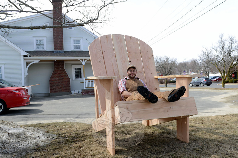 Doug Calderone sits on Queen Street in the chair he crafted for a raffle, which will benefit the Collaborative Recovery Fund. (Bobowick photo)
