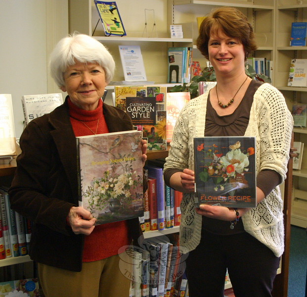 Beryl Harrison (left) and Kerri Williams show off the two books recently donated to C.H. Booth Library in memory of the late Pat Benkovich, a longtime member of The Garden Club of Newtown. (Hicks photo)