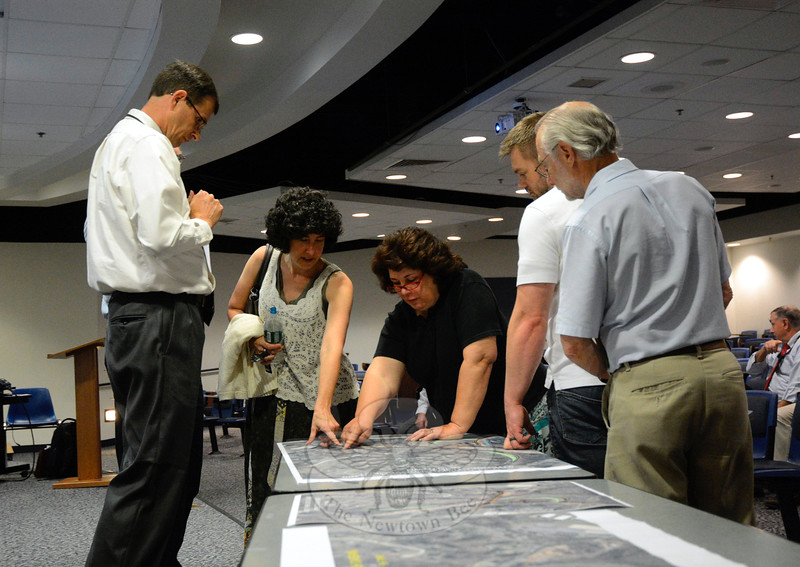 Paul Metsack, Jr, a project engineer with the state Department of Transportation (DOT), left, looks on as Deborra Zukowski, second from left, among others, review a modified aerial photo that depicts various changes that the DOT is planning for I-84's Exit 11 interchange and surrounding area. The changes are intended to reduce traffic congestion and reduce the frequency of motor vehicle accidents in the area. (Gorosko photo)