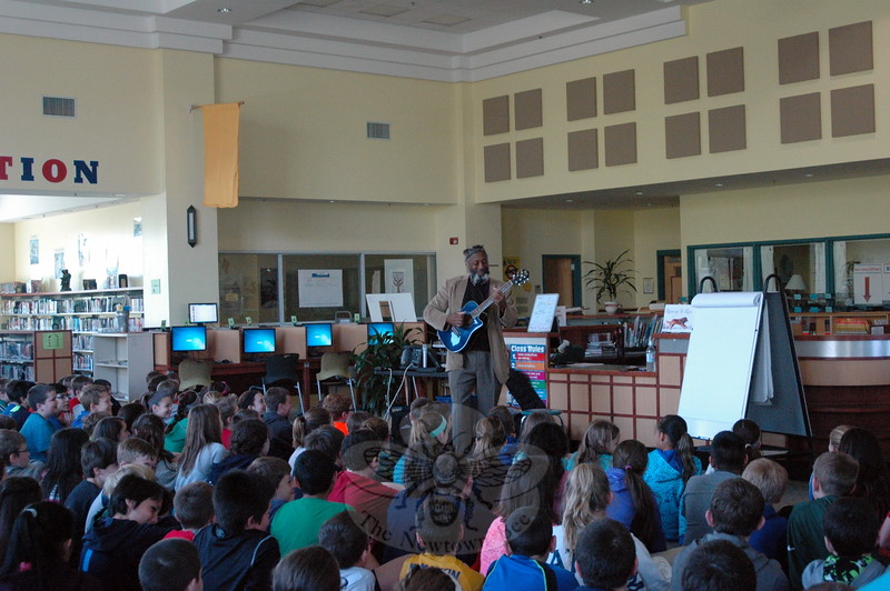 Storyteller Eshu Bumpus played a guitar while sharing a story with Reed Intermediate School students on Monday, May 4, ahead of a writing workshop he oversaw. (Hallabeck photo)