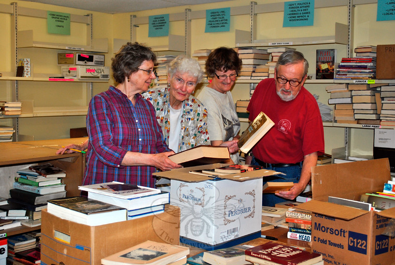 From left, volunteers with Friends of the C.H. Booth Library Denise Kaiser, Carm O'Neill, Carol Benson, and Jack Hickey-Williams look over book donations. Shoppers at the Annual Book Sale, July 11 to 15, will find plenty for books ideal for summer reading, they said. (Crevier photo)