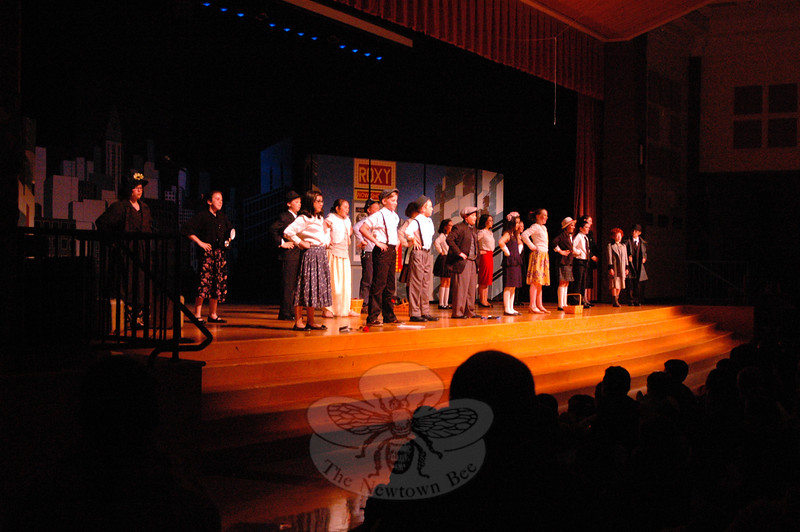 "While singing ""N.Y.C."" during their assembly presentation of Annie Jr, cast members gathered on the stage at Reed Intermediate School. (Hallabeck photo)"