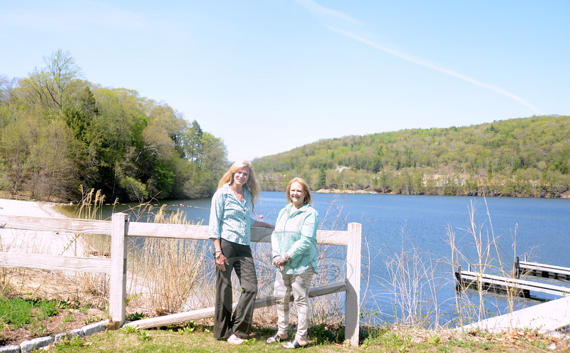 Parks and Recreation Director Amy Mangold, left, and the department's rental agent Deborah Denzel stand in a picnic area overlooking an inlet on Lake Zoar where the town now operates a marina, its edge visible on the right, and a small beach, left. (Bobowick photo)