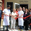 "Owner Denis Demiril, with scissors, is surrounded by staff including chefs Bledar Thaci and Vinny Meyer, family members including his wife, Marita, First Selectman Pat Llodra, and Economic Development Commission officials Jean Leonard and Matthew Mihalcik May 4 at a grand opening ribbon-cutting celebrating Soho Pizza at 123 South Main Street. The town's newest pizza purveyor is open seven days a week in the Highland Plaza offering ""Nonna Maria's"" special recipe eat-in or takeout thin crust New York-style pies, paninis, salads, wraps, and tasty gelato. (Voket photo)"