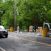 On May 20, an SUV travels southward on Glen Road in Sandy Hook, near a construction staging area that has been built for the state's upcoming renovation of the Silver Bridge, left background. Positioned above the SUV are two shrouded traffic signals, which will be among the signals in use to regulate alternating two-way traffic that will travel across the span when the work is underway on the $4.47 million project. The truss-style bridge across the Lake Zoar section of the Housatonic River, which was built in 1936, links Glen Road to River Road in Southbury. (Gorosko photo)