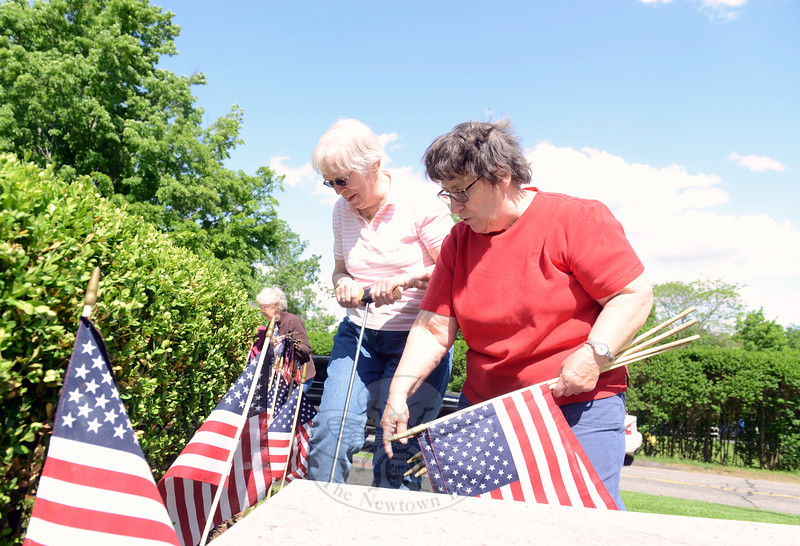 Coke Cramer and Marion Thompson place flags in the ground surrounding a circular hedge at the base of the monument. (Bobowick photo)