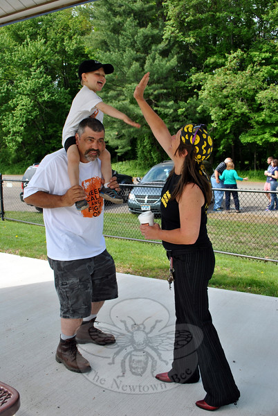"""Kat Holick, Newtown's dancing traffic agent, high-fives 3-year-old Ryan Costa, seated on father Gary Costa's shoulders. Ryan's mother, Julie Barbeau, challenged Ms Holick to take on TV talk show host Ellen Degeneres's """"Just Keep Dancing"""" challenge, to raise awareness of pediatric cancer. Ryan is currently undergoing treatment for leukemia, """"and doing really well,"""" according to Ms Barbeau. Approximately two dozen people popped up on the Dickinson Park field Monday morning, May 25, to join Ms Holick and Ryan, as they danced to """"Play It Again"""" by Luke Ryan, with sound provided by Linda Perrault. """"I'm honored!"""" exclaimed Ms Holick. """"That little boy has the cutest smile you've ever seen."""" A video of the challenge will be sent to Ellen Degeneres, said Ms Holick, who issued a continuing challenge to """"Just Keep Dancing"""" to pop stars Pink and Cher, and Laurie Pineau and the Sunshine Kids. """"I just wanted [Kat] to do a video of herself. I never thought it would get this big,"""" laughed Ms Barbeau. (Crevier photo)"""