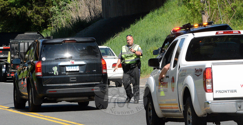 On May 22, a Newtown police officer walks amid traffic on Berkshire Road, near its intersection with Wasserman Way, as police held the Click-It or Ticket enforcement project, checking on whether motorists were wearing seatbelts as required by state law. Newtown, Redding, Bethel, and Brookfield police joined forces during the project, conducting heavy enforcement in each of those four towns.  The nationwide enforcement project runs through May 31. (Gorosko photo)
