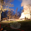 Firefighters continued to pour water on the collapsed house at 4 Aunt Park Lane more than an hour after arriving on the scene Monday morning. A stubborn fire, fueled by compressed gas within two large propane tanks close to the dwelling, destroyed the Cape-style house. All three occupants were able to escape without injury. (Hicks photo)