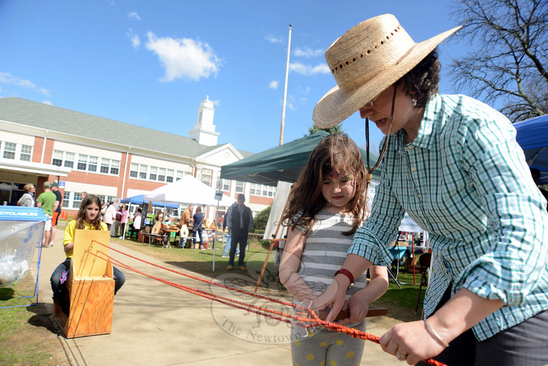 Christin Dixcy holds a rope and helps Beatrice Tucker as she works to braid strands of rope into a jump rope at the 8th Annual Newtown Earth Day Festival on Saturday, May 2.. At the far end is Lilly Chenoweth, turning a handle that twisted the sections of rope together.	—Bee Photo, Bobowick