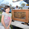 Nicole Bojarczyk stands beside a see-through beehive from beekeeper and resident Jeff Shwartz at the 8th Annual Newtown Earth Day Festival on Saturday, May 2.. Guests could look through the hive's glass sides and watch the bees bustle as they work. (Bobowick photo)
