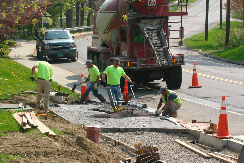 Rob Manna, the owner of LRM Inc, runs a power screed on Tuesday, May 5, to level the concrete on a new driveway apron at 3 Church Hill Road, while LRM employees manually check the just-poured materials trucked in by F&F Concrete of Plantsville. Mr Manna's company has been installing the first section of a Memorial Sidewalk, a project that was put in motion shortly after 12/14 to connect Main Street to Sandy Hook Center with sidewalks. A stone retaining wall has been built alongside the top of Church Hill Road, and work has resumed after a winter break on the sidewalk and curbing. Tuesday's work was at the easternmost point of the current project, and will connect to a sidewalk that already runs from 3 Church Hill Road down to the roadway's intersection with Wendover Road.  (Hicks photo)