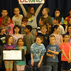 "After first singing their school's song, Middle Gate Elementary School fourth graders shared a number of songs during an assembly on Thursday, April 23, as a preview for their then-upcoming Spring Concert, which was held in the evening of April 27. Led by Middle Gate music teacher Tina Jones, the students sang songs like, ""Don't Worry, Be Happy,"" ""Pizza Love,"" ""Happy,"" and ""Nothing More."" When the group sang ""Nothing More,"" by the Alternate Routes, different students took turns holding up signs. Olivia Ayles, shown, held the ""be kind"" sign during the performance. (Hallabeck photo)"