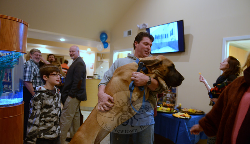 Resident Lee Tetreault hugs Max, Dr Vali's Great Dane pup. The dog visited with guests during an open house to show off renovations to the hospital space. (Bobowick photo)