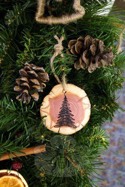 Handmade ornaments like this one — a slice of cedar with a hand-drawn evergreen tree — have been created for The Garden Club of Newtown's Annual Greens Sale this year. The event has an emphasis on handmade ornaments and natural materials, and is always a popular offering during one of the busiest weekends in town. (Hicks photo)