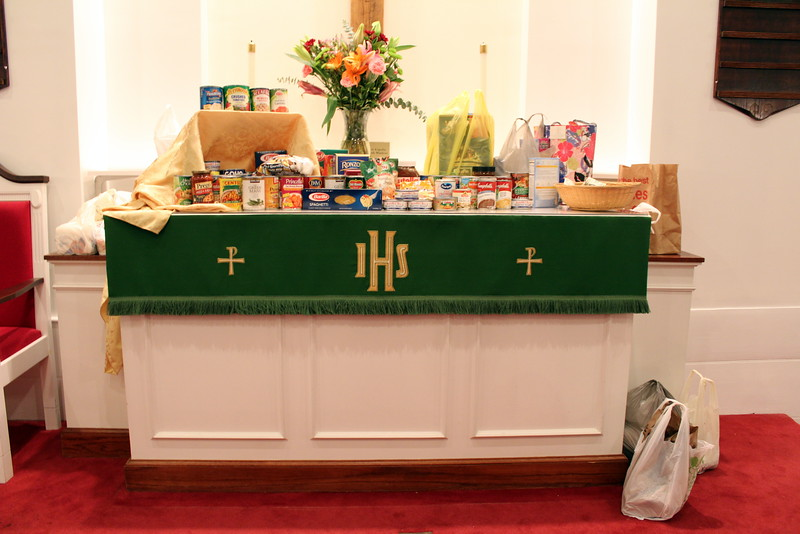 Sunday's offering was promised to FAITH Food Pantry, the nonecumenical food pantry based in St John's Episcopal Church. Guests of the Interfaith Thanksgiving Gathering covered the Communion table, a ledge behind it, and even a small area of the floor within the church's chancel with donations. A basket near the right of the table received financial donations that were also to be forwarded to the pantry. (Hicks photo)
