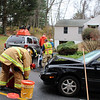 Sandy Hook Firefighter John Moore checks the roadway for fluids and vehicle debris following a two-car accident in front of 12 Buttonball Drive around 1:15 pm Thursday, November 19, while other firefighters check on the driver of one of the vehicles. Police report that a compact Volkswagen driven by Elizabeth Melega, 50, of Taunton, Mass., struck the rear end of an unspecified vehicle driven by Brian Olszewski, 21, of 4 Old Green Road. Melega received a minor injury, police said. An ambulance crew also responded to the accident. Police report they charged Melega with driving under the influence and with failure to drive a reasonable distance apart. Melega was released on $500 bail for a December 3 court appearance, according to police. (Hicks photo)