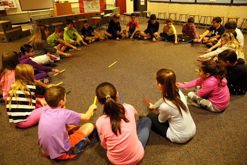 """Head O' Meadow Elementary School music teacher Cynthia Holberg, seated upper left, taught her students on Thursday, November 19, how to sing a song, called """"Al Citron,"""" in Spanish and to play the stick passing game that accompanies the song. (Hallabeck photo)"""