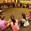 "Head O' Meadow Elementary School music teacher Cynthia Holberg, seated upper left, taught her students on Thursday, November 19, how to sing a song, called ""Al Citron,"" in Spanish and to play the stick passing game that accompanies the song. (Hallabeck photo)"