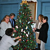 "Left, Sheila Torres, kneeling, operations manager at Edmond Town Hall, Laura Branchini, Newtown Junior Women's Club, and Neil Callghan, Golden Opportunities, and right, Susan Callaghan, Golden Opportunities, and Knettie Archard, director of Golden Opportunities, admire the ornaments and tags adorning the tree in the lobby of Edmond Town Hall, Monday morning, November 23. The Newtown Junior Women's Club and Golden Opportunities are collaborating this year for the Tag-A-Gift program, as part of the larger Holiday Basket drive led by The Newtown Fund. ""Giving trees/wreathes"" at eight locations, including Edmond Town Hall, are decorated with wishes, which organizers hope will be adopted by residents and help make holiday dreams come true for the less fortunate. (Crevier photo)"