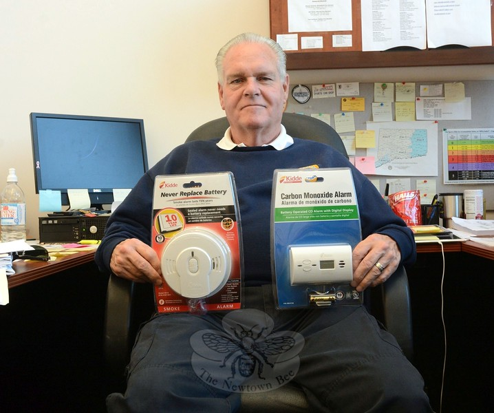 Fire Marshal Bill Halstead, at his office at Newtown Municipal Center, displays the two types of fire safety devices that the town is providing free to people in need — a smoke detector and a carbon monoxide detector. (Gorosko photo)