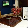 A massive chocolate cake decorated with the Newtown Country Club's insignia, which was baked in honor of the organization's 100th anniversary, was positioned next to a citation from the state's General Assembly noting the group's centennial.  (Gorosko photo)