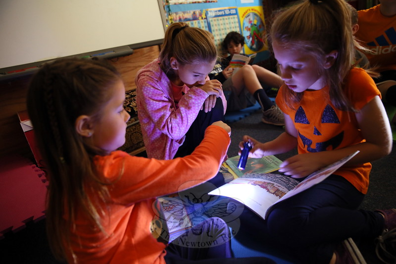 Hawley Elementary School students, from left, kindergartener Ava Keil, and fourth graders Sara Premus and Makenzie Del Poso read Little Dog Lost by flashlight on Friday, October 30. Students across the school that day buddied up to read their favorite fall or Halloween stories with the lights turned off. (Hallabeck photo)