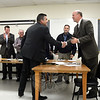 James Viadero, standing left foreground, shakes hands with Police Chief Michael Kehoe at the Tuesday, November 3, Police Commission meeting at which the commission named Mr Viadero as the town's new police chief. Standing in the background are, from left, commission members Andrew Sachs and Joel Faxon, Chairman Paul Mangiafico, and Virgil Procaccini, Jr. Member Brian Budd is not visible in the photo. (Gorosko photo)