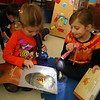 Hawley first grader Piper Feli, left, and kindergartener Lia Spremullo read Bear Feels Scared by flashlight last Friday. (Hallabeck photo)