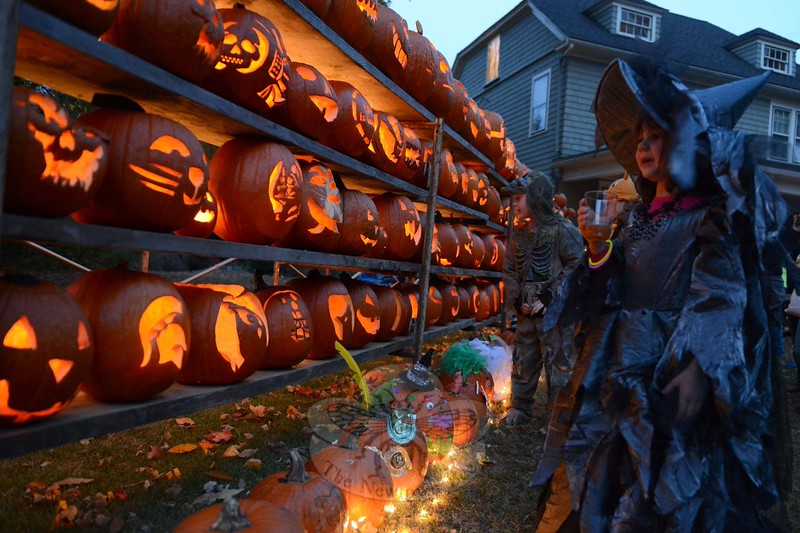 A pair of children in costumes were among those who slowed down on Halloween to take an up-close look at the pumpkins on display at 14 Main Street. (Bobowick photo)