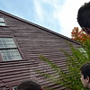 Newtown High School architectural design students looked up at a top window of the Matthew Curtiss House as Town Historian Dan Cruson pointed out the differences between the lower window and the higher window. (Hallabeck photo)